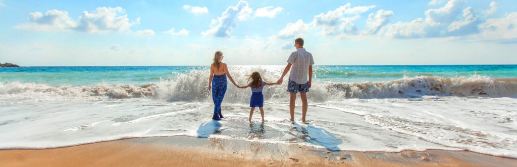 Family on beach in waves